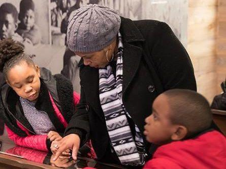 a woman and two children reading a plaque in a museum