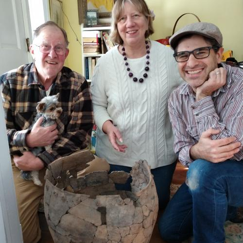 Andrea Lain, archaeology collections manager, and archaeology technician Ralph Rataul pose with Jim Veith Jr. and his dog Scooter, along with the Suffern Rockshelter pot.